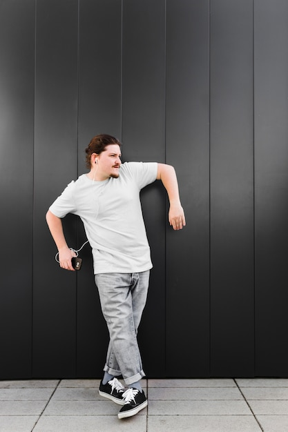 Hörende musik des jungen mannes auf kopfhörer durch den handy, der gegen schwarze wand steht Kostenlose Fotos