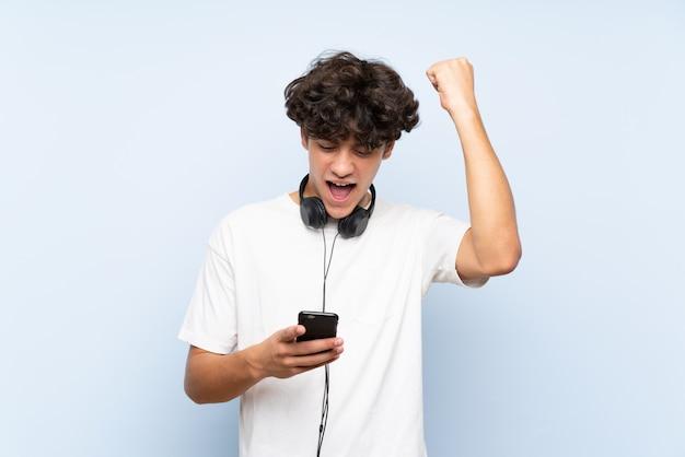 Hörende musik des jungen mannes mit einem mobile über der lokalisierten blauen wand, die einen sieg feiert Premium Fotos