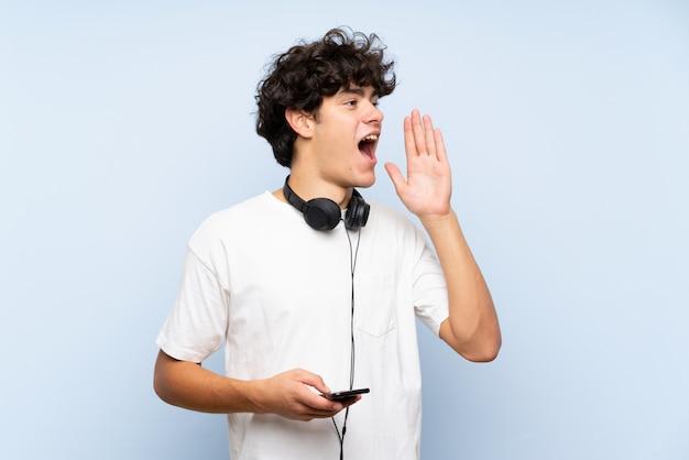 Hörende musik des jungen mannes mit einem mobile über der lokalisierten blauen wand, die mit dem breiten mund schreit, öffnen sich Premium Fotos