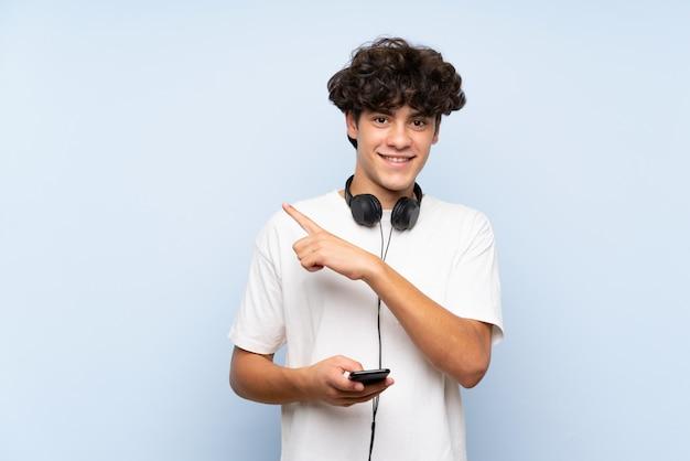 Hörende musik des jungen mannes mit einem mobile über lokalisierter blauer wand zeigend auf die seite, um ein produkt darzustellen Premium Fotos