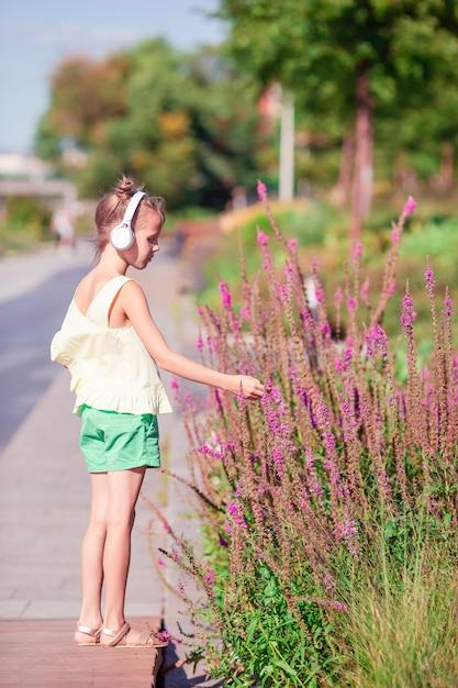 Hörende musik des kleinen entzückenden mädchens im park Premium Fotos