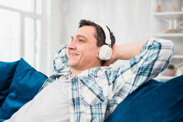 Hörende musik des netten mannes in den kopfhörern auf sofa Kostenlose Fotos