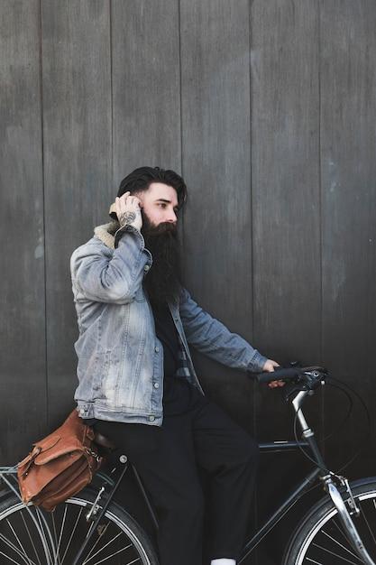 Hörende musik des radfahrers auf den kopfhörern, die gegen schwarze hölzerne wand stehen Kostenlose Fotos