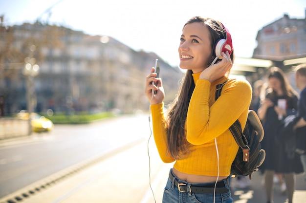Hörende musik des schönen mädchens mit kopfhörer beim gehen in die straße Premium Fotos