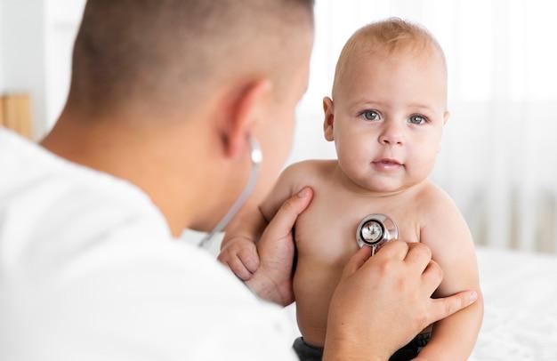 Hörendes kleines baby hinteren ansichtdoktors mit stethoskop Kostenlose Fotos