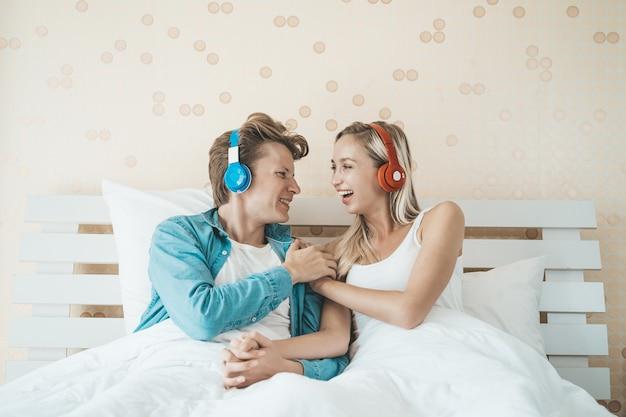 Hörendes lied des glücklichen paars morgens am schlafzimmer Kostenlose Fotos