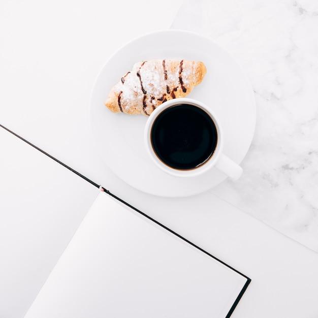 Hörnchen und kaffeetasse auf platte nahe dem leerseitennotizbuch Kostenlose Fotos