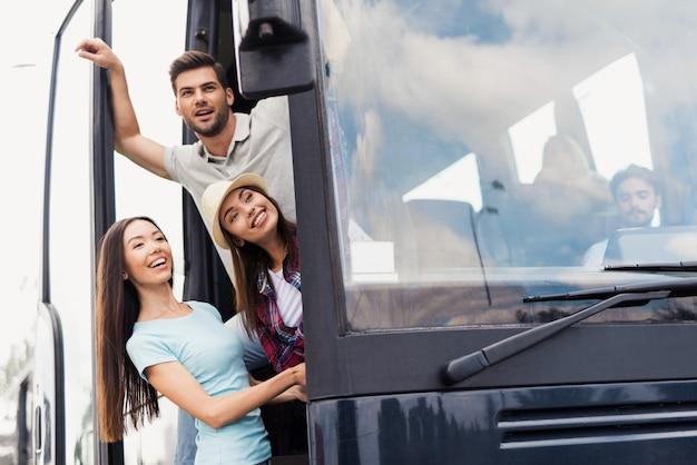 Hoffnungsvolle junge leute an der tür des reisebusses. Premium Fotos