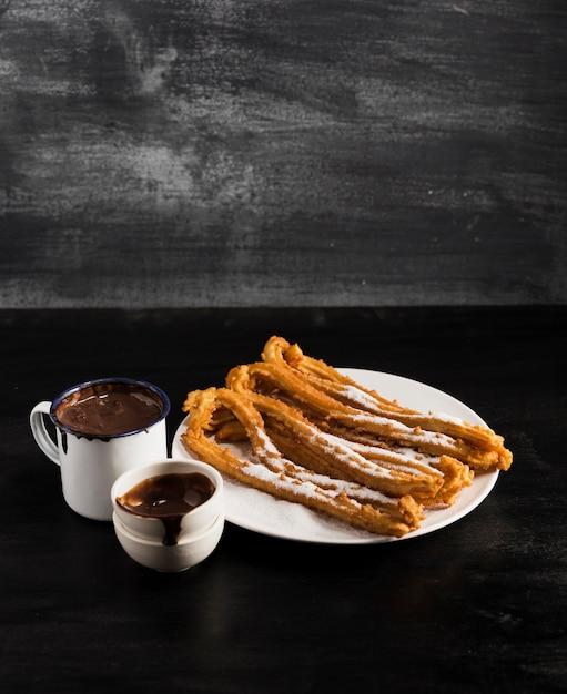 Hohe ansicht briet churros auf einer platte mit bechern schokolade Kostenlose Fotos