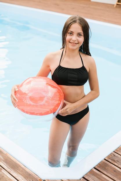 Hohe ansicht des weiblichen kindes einen wasserball halten Kostenlose Fotos