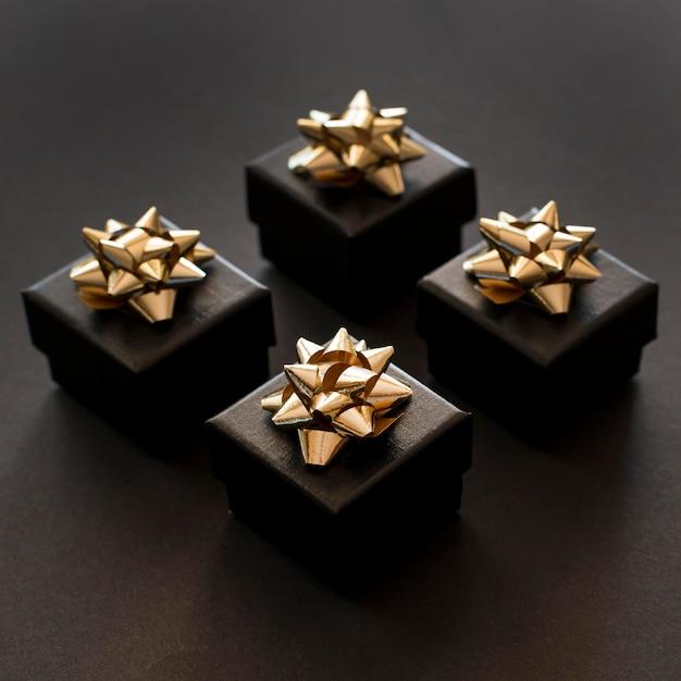 Hohe ansicht schwarze geschenkboxen mit goldenen bändern Kostenlose Fotos