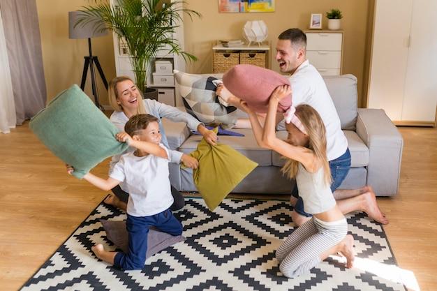 Hohe ansichtfamilie, die mit kissen spielt Kostenlose Fotos
