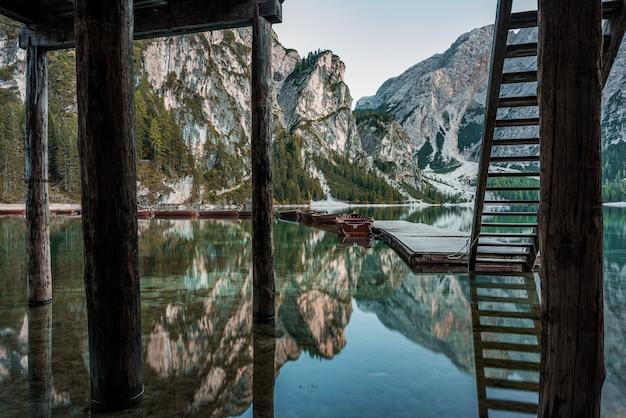 Hohe felsige berge spiegelten sich im braies-see mit holztreppen nahe dem pier in italien wider Kostenlose Fotos
