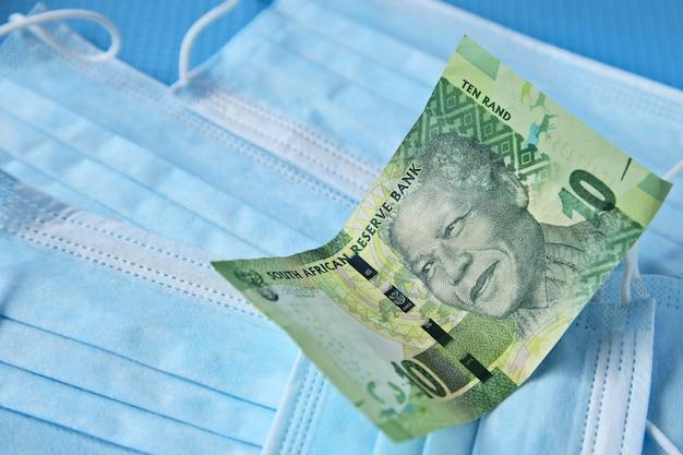 Hohe winkelansicht einer banknote auf einigen operationsmasken auf einer blauen oberfläche Kostenlose Fotos