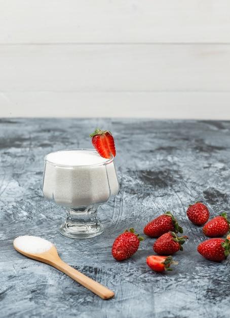 Hohe winkelansicht einer glasschale joghurt auf weiden-tischset mit holzlöffel und erdbeeren auf dunkelblauem marmor und weißem holzbretthintergrund. vertikaler freier speicherplatz für ihren text Kostenlose Fotos