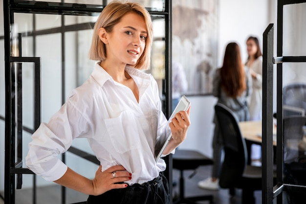 Hohe winkelfrau, die an tablette arbeitet Kostenlose Fotos