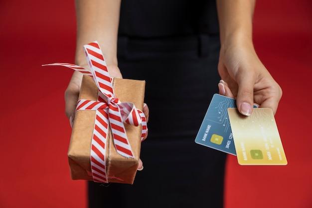 Hohe winkelfrau, die kreditkarten und geschenk hält Kostenlose Fotos