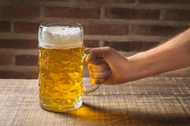 Hohe winkelhand, die halbes liter mit bier auf tabelle hält Kostenlose Fotos