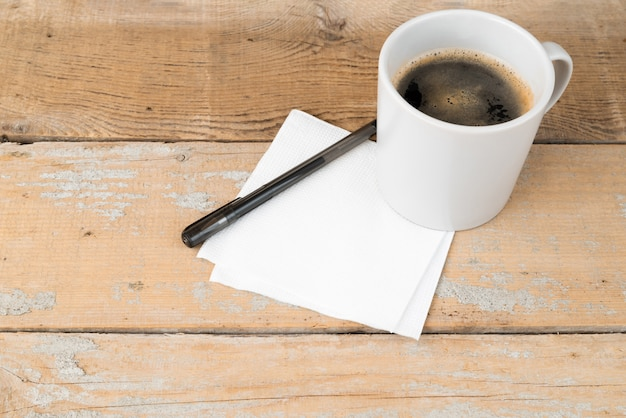 Hohe winkelkaffeetasse auf hölzernem hintergrund Kostenlose Fotos