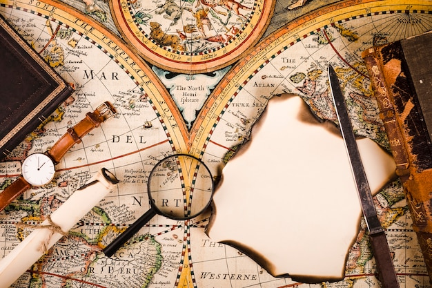 Hohe winkelsicht der armbanduhr, der lupe, des gebrannten papiers und des messers auf karte Kostenlose Fotos