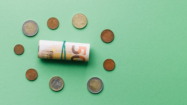 Hohe winkelsicht der aufgerollten eurobanknote mit münzen auf grünem hintergrund Kostenlose Fotos
