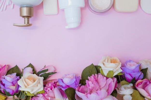 Hohe winkelsicht der feuchtigkeitscreme und der gefälschten blumen auf rosa hintergrund Kostenlose Fotos
