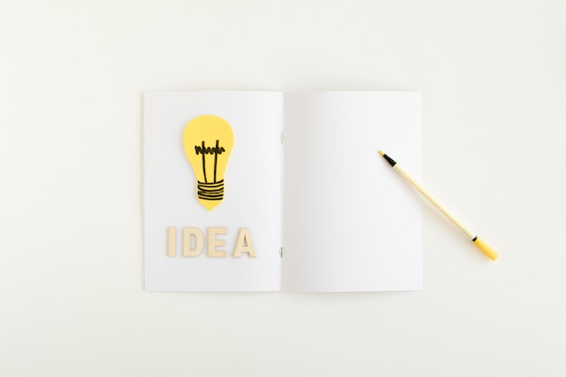 Hohe winkelsicht der gelben glühlampe mit ideentext auf weißer karte Kostenlose Fotos