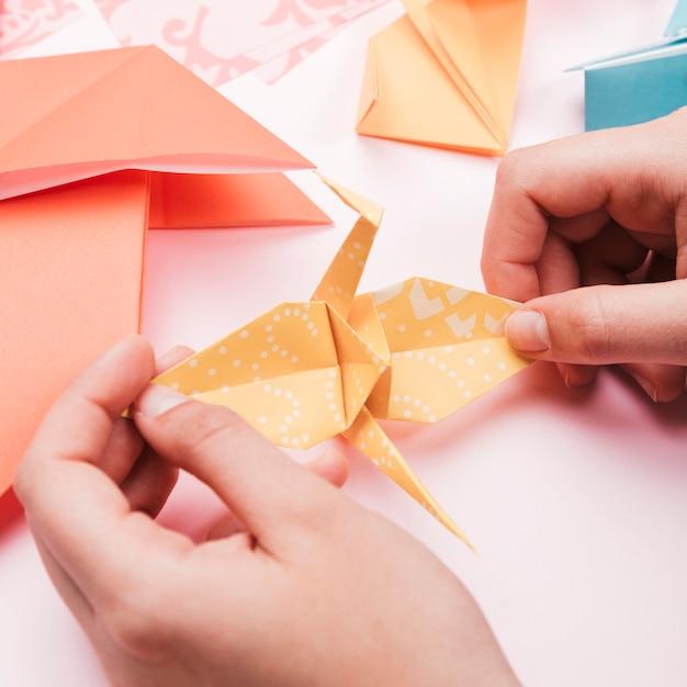 Hohe winkelsicht der künstlerhand origamipapiervogel halten Kostenlose Fotos