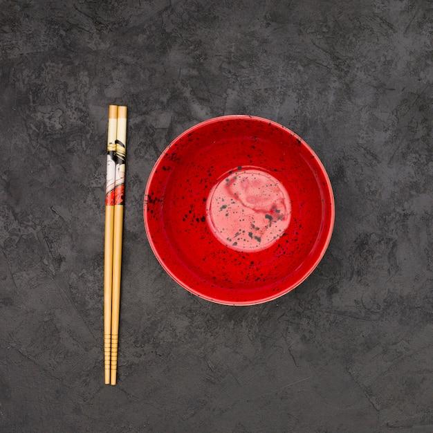 Hohe winkelsicht der leeren chinesischen schüssel und der hölzernen essstäbchen über strukturiertem schwarzem hintergrund Kostenlose Fotos