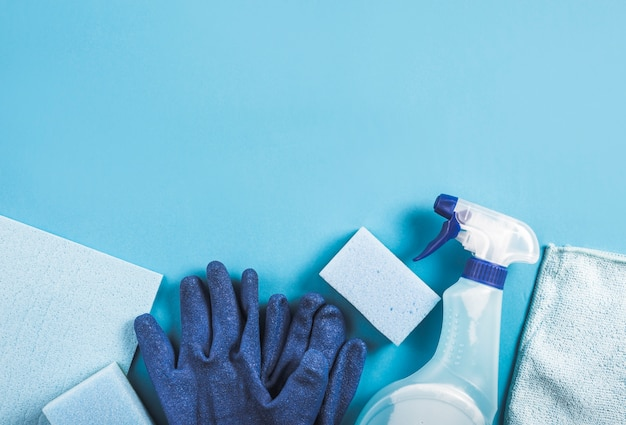 Hohe winkelsicht der sprühflasche, der handschuhe und des schwammes auf blauem hintergrund Kostenlose Fotos