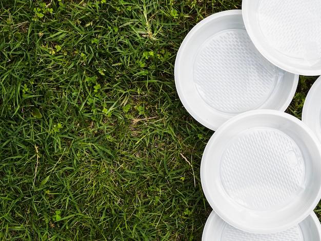 Hohe winkelsicht der weißen leeren plastikplatte auf gras Kostenlose Fotos