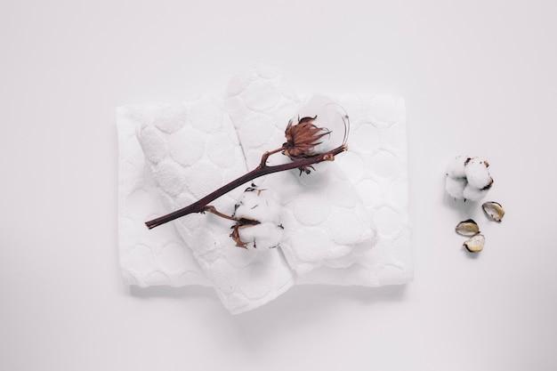 Hohe winkelsicht des baumwollzweigs und -servietten auf weißer oberfläche Kostenlose Fotos