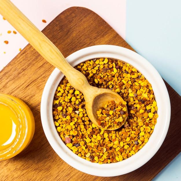 Hohe winkelsicht des blütenstaubs und des honigs auf hölzernem schneidebrett Kostenlose Fotos