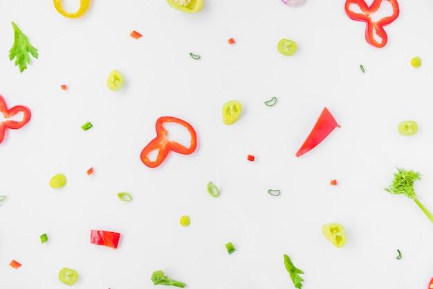 Hohe winkelsicht des bunten geschnittenen gemüses auf weißem hintergrund Kostenlose Fotos