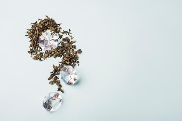 Hohe winkelsicht des diamanten und der trockenen blumenblumenblätter auf weißer oberfläche Kostenlose Fotos