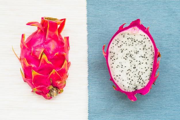 Hohe winkelsicht des drachen trägt auf bunte tischdecke früchte Kostenlose Fotos