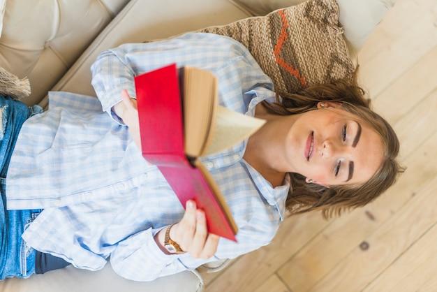 Hohe winkelsicht des frauenlesebuches beim lügen auf sofa Kostenlose Fotos