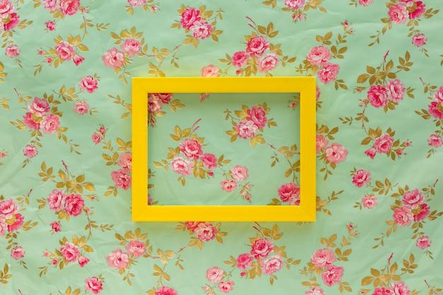 Hohe winkelsicht des gelben leeren rahmens gegen blumendruckhintergrund Kostenlose Fotos