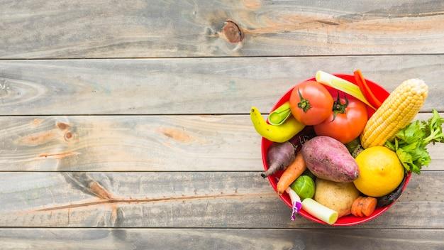 Hohe winkelsicht des gesunden gemüses in der schüssel auf hölzerner planke Kostenlose Fotos