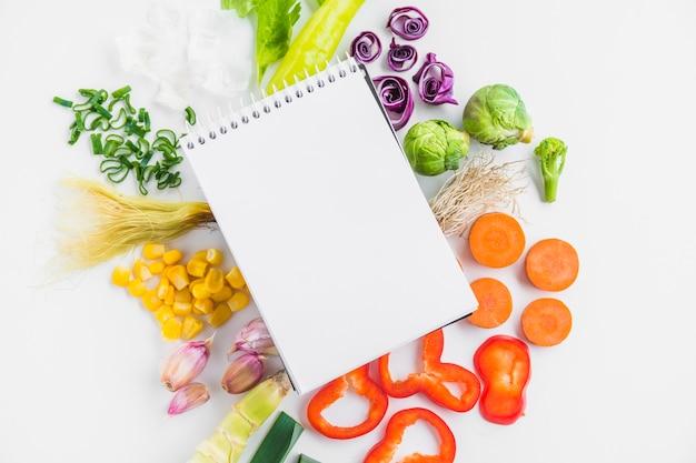 Hohe winkelsicht des gesunden rohen gemüses und des gewundenen notizblockes Kostenlose Fotos
