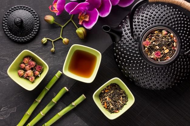 Hohe winkelsicht des getrockneten krautbestandteils und des bambusstocks mit orchideenblume Kostenlose Fotos