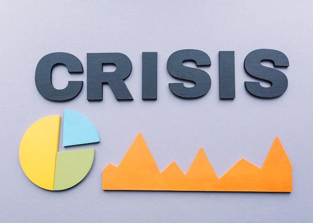 Hohe winkelsicht des krisenwortes mit diagrammen auf grauem hintergrund Kostenlose Fotos