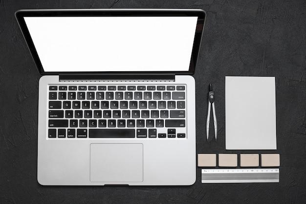 Hohe winkelsicht des laptops und der briefpapiere auf schwarzem hintergrund Kostenlose Fotos