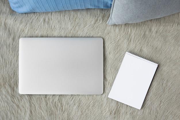 Hohe winkelsicht des laptops und des gewundenen notizblockes auf sofa Kostenlose Fotos