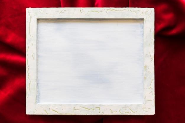 Hohe winkelsicht des leeren bilderrahmens auf glattem rotem gewebe Kostenlose Fotos
