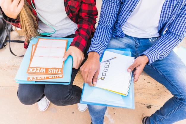 Hohe winkelsicht des männlichen und weiblichen studenten, der wöchentlichen zeitplan plant Kostenlose Fotos
