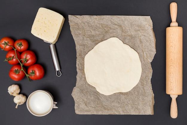 Hohe winkelsicht des reihenbestandteils und des herausgerollten pizzateigs auf pergamentpapier mit hölzernem nudelholz über schwarzer oberfläche Kostenlose Fotos