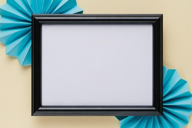 Hohe winkelsicht des schwarzen hölzernen grenzfotorahmens mit blauem origamifan auf beige hintergrund Kostenlose Fotos