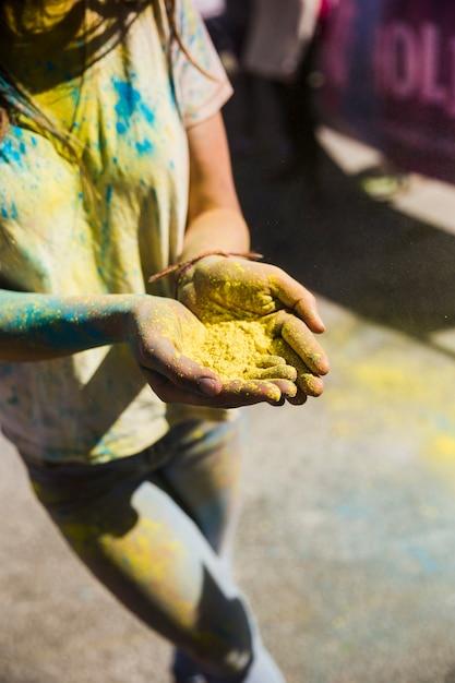 Hohe winkelsicht einer frau, die in der hand gelbe farbe hält Kostenlose Fotos