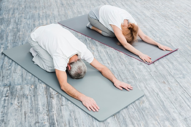 Hohe winkelsicht eines paares in der weißen ausstattung, die yoga-positionen ausdehnend übt Kostenlose Fotos